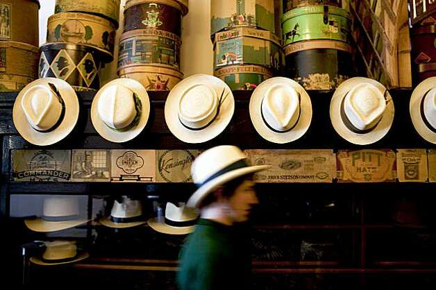 Abbie Dwelle walks past a row of hats. Photo: Stephen Lam, The Chronicle