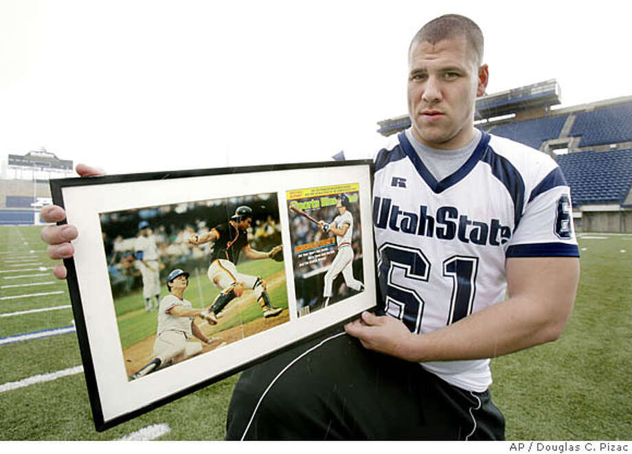 Utah State offensive lineman Shawn Murphy holds framed pages from Sports Illustrated showcasing his father, major league baseball player Dale Murphy, Wednesday, April 16, 2007, in Logan, Utah. The son of the two-time National League MVP, Shawn gave up playing baseball late in high school so he could focus on football. Eight years later, it may have been a career decision as he waits for the NFL draft. (AP Photo/Douglas C. Pizac) Photo: Douglas C. Pizac