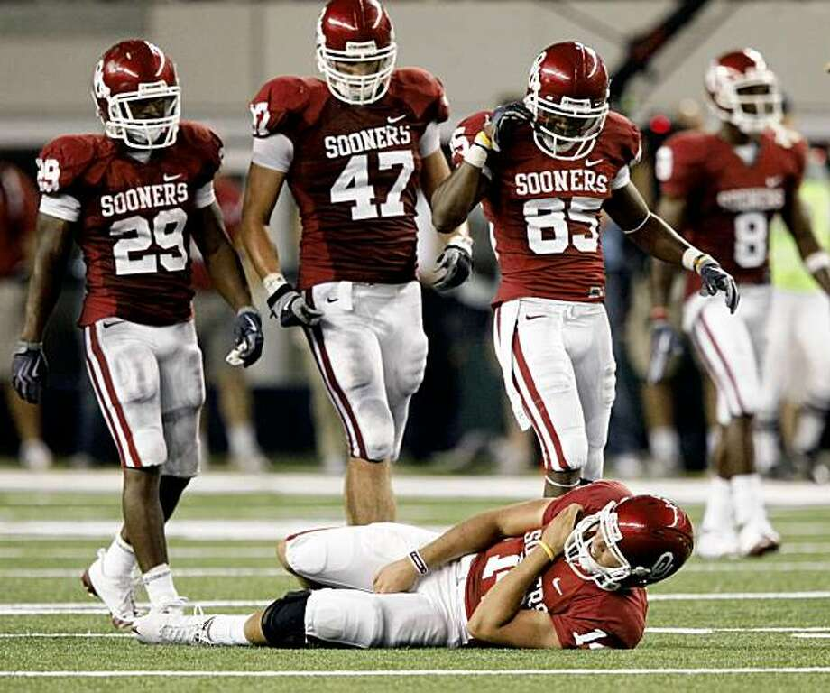 Teammates look to Oklahoma quarterback Sam Bradford who lies on the field after being hit by BYU's Coleby Clawson in the second quarter of an NCAA college football game Saturday, Sept. 5, 2009, in Arlington, Texas. Bradford left the game. (AP Photo/Dallas Morning News,Tom Fox) ** MANDATORY CREDIT; NO SALES; MAGAZINES OUT; TV OUT; INTERNET USE BY AP MEMBERS ONLY ** Photo: Tom Fox, AP