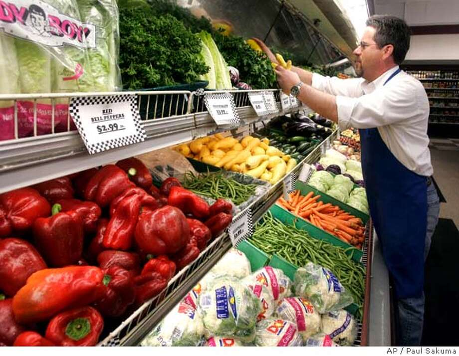 John Garcia, of JJ&F Market, organizes vegetables on display at a grocery store in Palo Alto, Calif., Tuesday, April 15, 2008. Inflation at the wholesale level soared in March at nearly triple the rate that had been expected as the costs of energy and food both climbed rapidly. (AP Photo/Paul Sakuma) Photo: Paul Sakuma