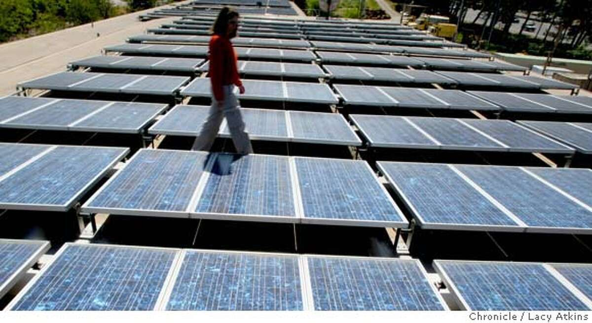 ###Live Caption:Dana Armanino, Solar Project Coordinator of the County of Marin check the 503 solar panels, Tuesday April 15, 2008, at the Civic Center in San Rafael, Calif. Marin is kicking off a public education campaign, called Marin Clean Energy, which will allow customers to buy either