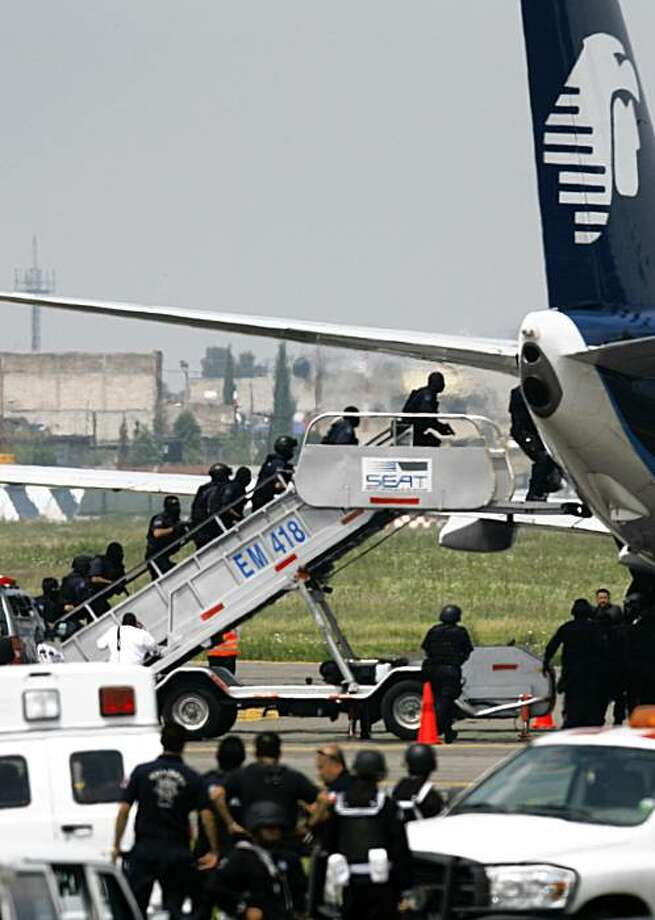 Police prepare to enter a hijacked Aeromexico plane sitting on the tarmac at Mexico City's international airport, Wednesday, Sept. 9, 2009.  (AP Photo/Marco Ugarte) Photo: Marco Ugarte, AP