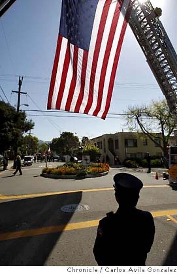 A Berkeley waits under the American flag for the memorial procession to arrive on Addison Street. Hundreds of firefighters from Berkeley Fire Department and surrounding agencies took part in a memorial procession down Shattuck Avenue in Berkeley, Calif., on Saturday, April 12, 2008, for , Jay Walter, who passed away April 6th.  Photo by Carlos Avila Gonzalez / San Francisco Chronicle Photo: Carlos Avila Gonzalez