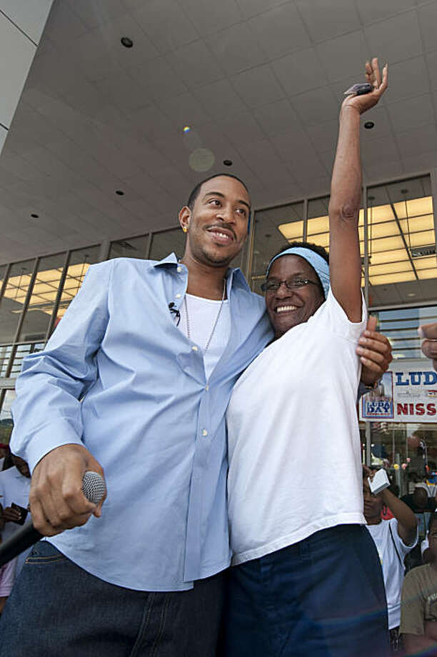 Rapper Ludacris smiles as Ella Me Johnson reacts to being presented with keys to her car at Nissan South, Sunday, Sept. 6, 2009 in Morrow, Ga.. Ludacris, The Ludacris Foundation and Nissan South partnered to give away 20 used vehicles to selected Metro Atlanta area residents as part of his LudaDay weekend. (AP Photo/Paul Abell) Photo: Paul Abell, AP