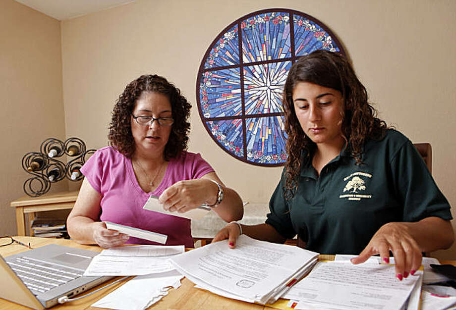 In this Aug. 19, 2009 photo, Veronica McGregor, left, and her daughter, Katie McGregor, 16, look over pay stubs and other financial information pertaining to Katie's first summer job as a swimming teacher at Hawthorne city pool, at their home in Redondo Beach, Calif. (AP Photo/Damian Dovarganes) Photo: Damian Dovarganes, AP