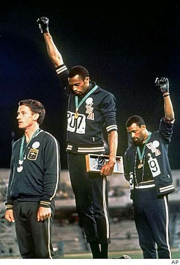 """Extending gloved hands skyward, United States athletes Tommie Smith, center, and John Carlos, right, stare downward during the playing of the """"Star-Spangled Banner"""" after Smith received the gold and Carlos the bronze for the 200 meter run at the Summer Olympic Games in Mexico City in this Oct. 16, 1968 file photo. Australia's silver medalist Peter Norman is at left. Photo: AP"""