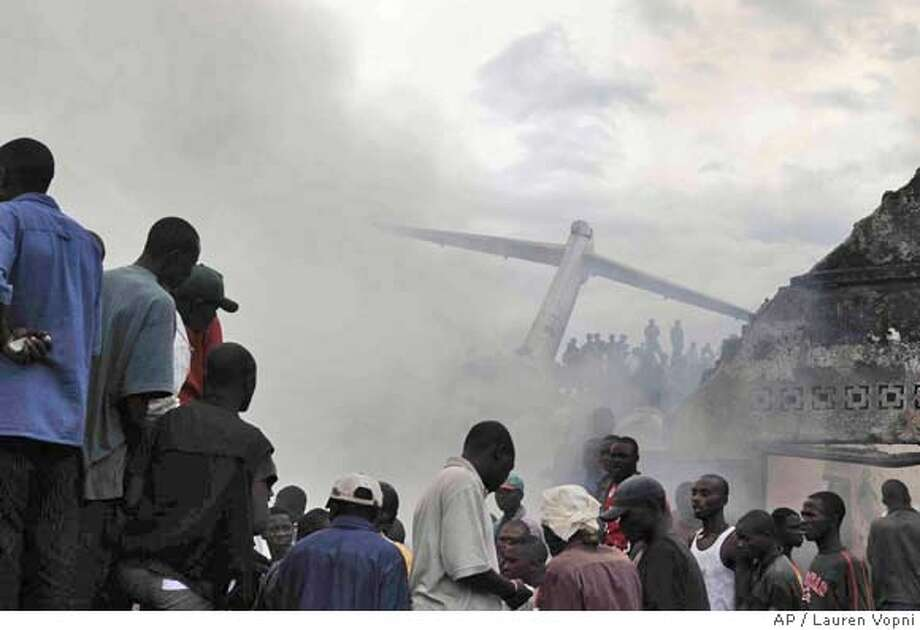 ###Live Caption:Rescue workers and onlookers gather at the site of a plane crash in Goma, Congo, Tuesday April 15, 2008. A passenger plane carrying 85 people crashed into a crowded neighborhood in the eastern Congo town Goma on Tuesday, and only six survivors have been found so far, government officials said. Smoke engulfed the charred ruins of the aircraft, which appeared to have broken in two when it slammed into the rooftops of about 10 cement homes just outside the airport, destroying them instantly. (AP Photo/Lauren Vopni)###Caption History:Rescue workers and onlookers gather at the site of a plane crash in Goma, Congo, Tuesday April 15, 2008. A passenger plane carrying 85 people crashed into a crowded neighborhood in the eastern Congo town Goma on Tuesday, and only six survivors have been found so far, government officials said. Smoke engulfed the charred ruins of the aircraft, which appeared to have broken in two when it slammed into the rooftops of about 10 cement homes just outside the airport, destroying them instantly. (AP Photo/Lauren Vopni)###Notes:###Special Instructions: Photo: Lauren Vopni