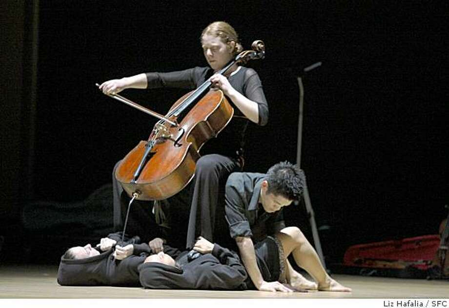 "Cellist Hannah Addario-Berry playing while sitting on Dudley Flores with dancers Kaitlyn Ebert and Tanya Bello on floor at the world premiere of ""Shipwreck"" at Yerba Buena Center for the Arts Forum on Thursday, April 10, in San Francisco, Calif.Photo by Liz Hafalia / San Francisco Chronicle Photo: Liz Hafalia, SFC"