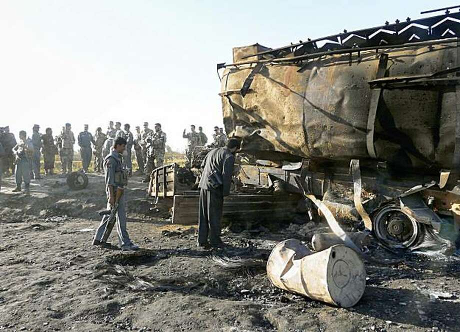 German soldiers with the NATO- led International Security Assistance Force (ISAF) , U.S. and Afghan forces are seen around one of the two fuel tankers which were bombed by a NATO jet on Friday in Kunduz, Kunduz  province, north of Kabul, Afghanistan, Saturday, Sept. 5, 2009.  The top U.S. commander in Afghanistan has confirmed villagers were injured at the site of a NATO airstrike on hijacked fuel tankers. (AP Photo) Photo: AP