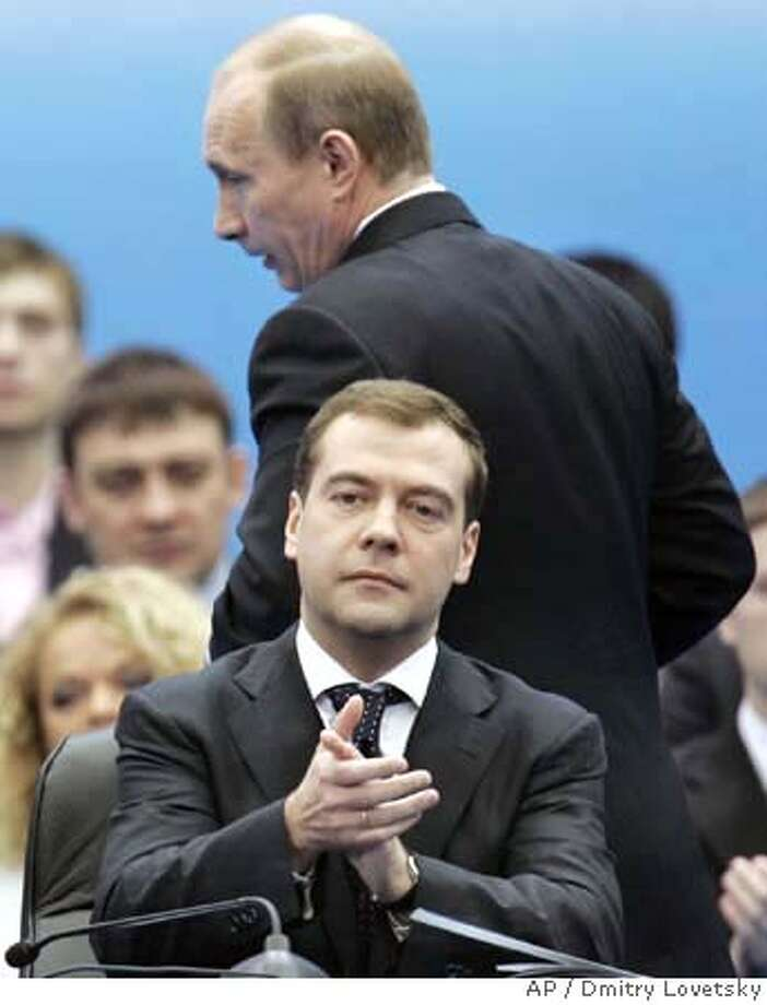###Live Caption:Russian President Vladimir Putin, background, walks to address a congress of the United Russia party in Moscow, Russia, Tuesday, April 15, 2008, as president-elect Dmitry Medvedev, front, applauds. Vladimir Putin accepted the leadership of the dominant United Russia party on Tuesday, securing his grip on power after he leaves the Kremlin and becomes prime minister next month. (AP Photo/Dmitry Lovetsky)###Caption History:Russian President Vladimir Putin, background, walks to address a congress of the United Russia party in Moscow, Russia, Tuesday, April 15, 2008, as president-elect Dmitry Medvedev, front, applauds. Vladimir Putin accepted the leadership of the dominant United Russia party on Tuesday, securing his grip on power after he leaves the Kremlin and becomes prime minister next month. (AP Photo/Dmitry Lovetsky)###Notes:Vladimir Putin, Dmitry Medvedev###Special Instructions:**ALTERNATIVE CROP OF MOSB106** Photo: Dmitry Lovetsky