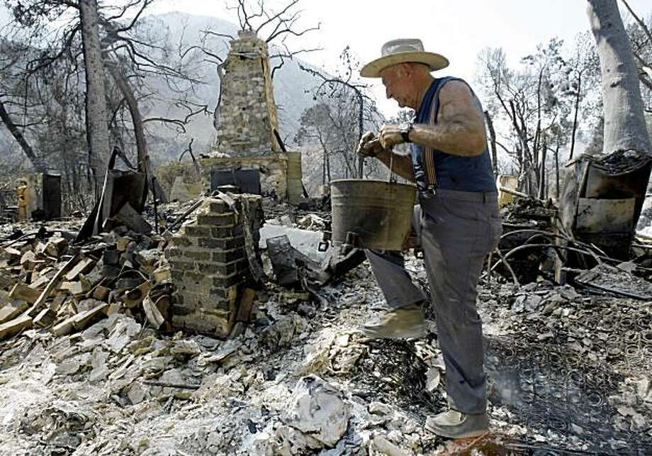 Lew Johnson, 74, carries a bucket of recovered items as he returns for the first time to the ruins of his home on Stonyvale Road in Big Tujunga Canyon in the Angeles National Forest, in the Tujunga area of Los Angeles, Friday, Sept. 4, 2009.  He had left his home for Canada on Aug. 28, the day before the Station Fire struck. He had no idea that the blaze, the largest in Los Angeles County history, had destroyed more than five dozen homes, including his own, and claimed the lives of two firefighters.  (AP Photo/Reed Saxon) Photo: Reed Saxon, AP