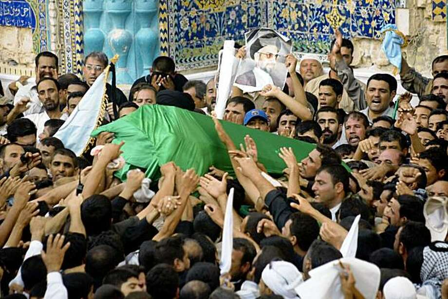 Shiite Muslim mouners try to touch the coffin of the late Shiite Muslim leader Abdel Aziz al-Hakim, head of the Supreme Iraqi Islamic Council (SIIC), in the southern holy city of Najaf, 160 kms from Baghdad, on August 29, 2009. Hakim, 60-years-old, was suffering from lung cancer and died at a hospital in Iran on August 26th. He was buried in Najaf next to his brother Ayatollah Mohammed Baqr al-Hakim who was assassinated in this holy city on August 29, 2003.  AFP PHOTO / QASSEM ZEIN (Photo credit should read QASSEM ZEIN/AFP/Getty Images) Photo: Qassem Zein, AFP/Getty Images