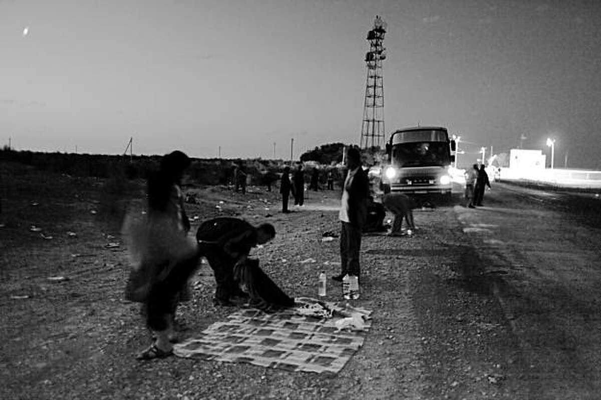 In this May 29, 2009 photo, Uzbek labor migrants traveling to Russia on a bus prepare to spend a night in the Kyzyl Kum desert in central Uzbekistan. Hundreds of thousands of Uzbeks flock to Russia annually in search of jobs. (AP Photo/Alexander Zemlianichenko)