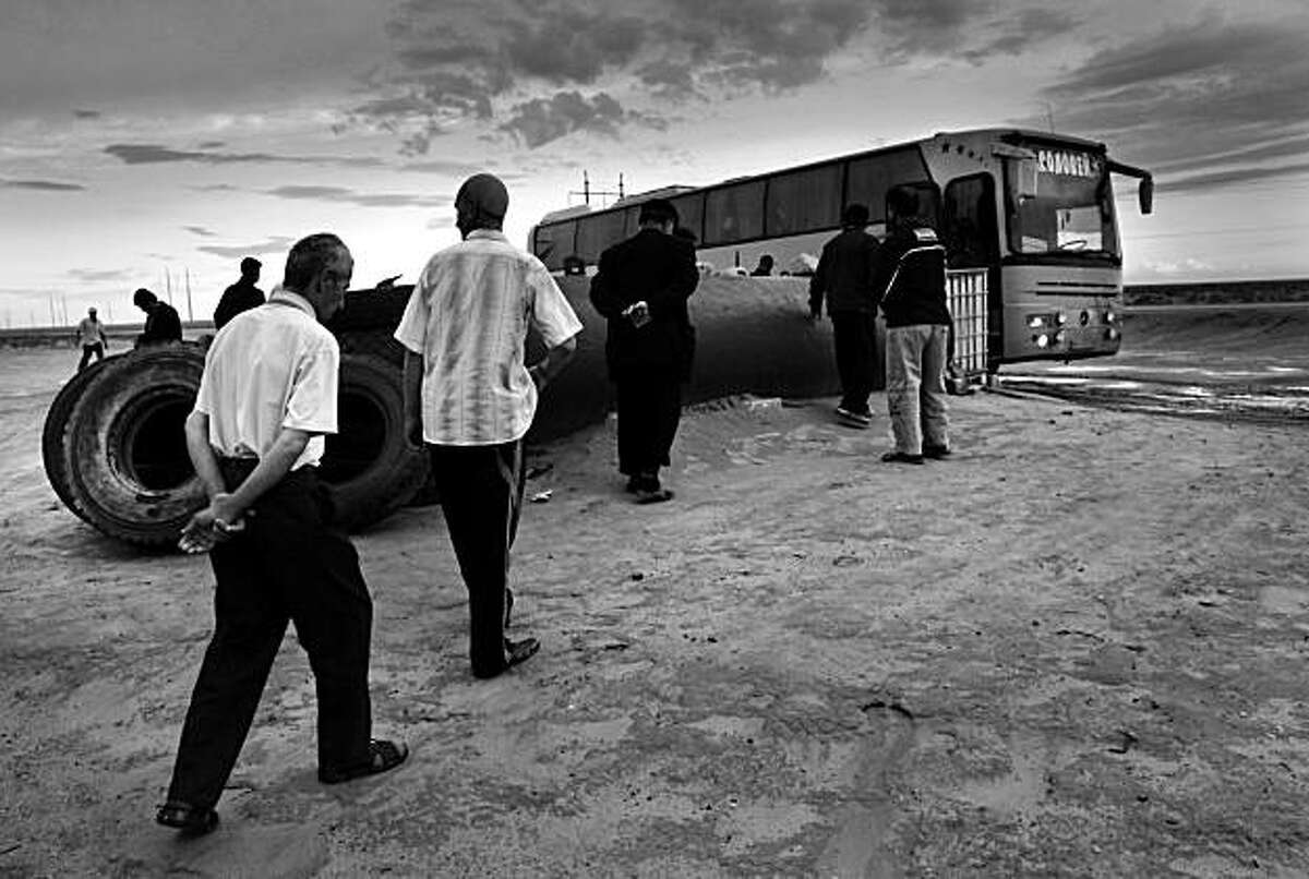 In this May 31, 2009 photo, Uzbek labor migrants approach their Russia-bound bus in the steppe of south-western Kazakhstan. Hundreds of thousands of Uzbeks flock to Russia annually in search of jobs. (AP Photo/Alexander Zemlianichenko)