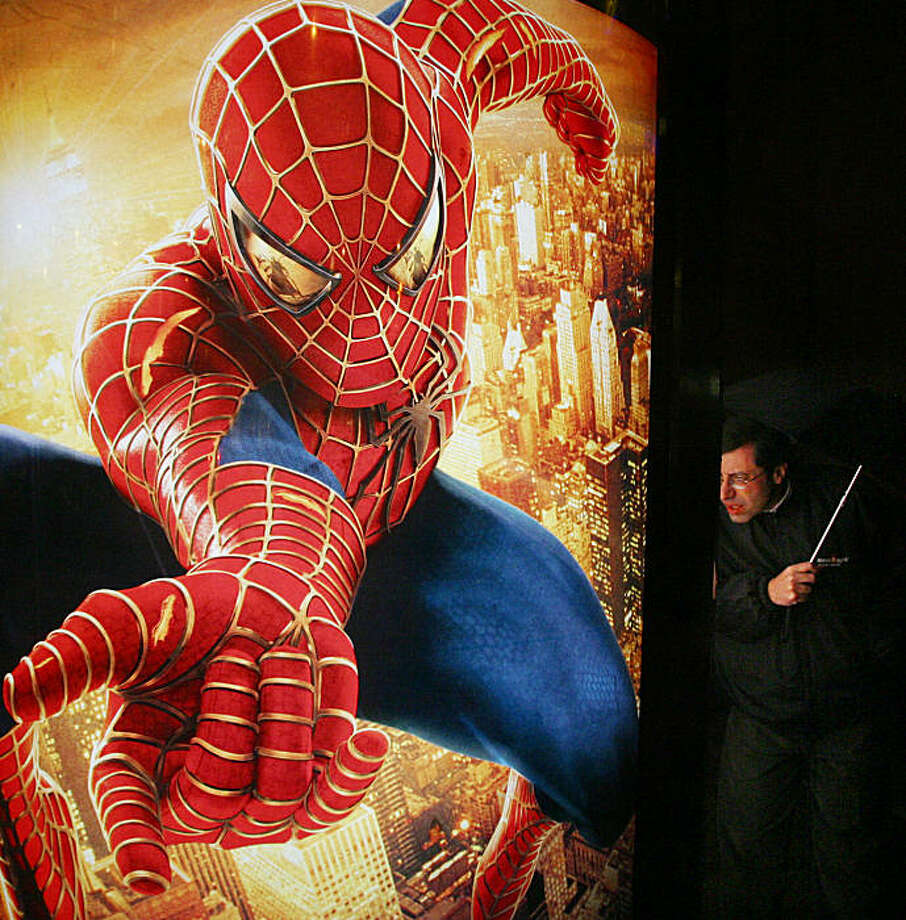 FILE - In this Nov. 11, 2004 file photo, a man looks at an advertisement for the Spider- Man movie in Copenhagen, Denmark. The Walt Disney Co. said Monday, Aug. 31, 2009, it is buying Marvel Entertainment Inc. for $4 billion in cash and stock, bringing such characters as Iron Man and Spider-Man into the family of Mickey Mouse and WALL-E.(AP Photo/John McConnico, file) Photo: John McConnico, AP
