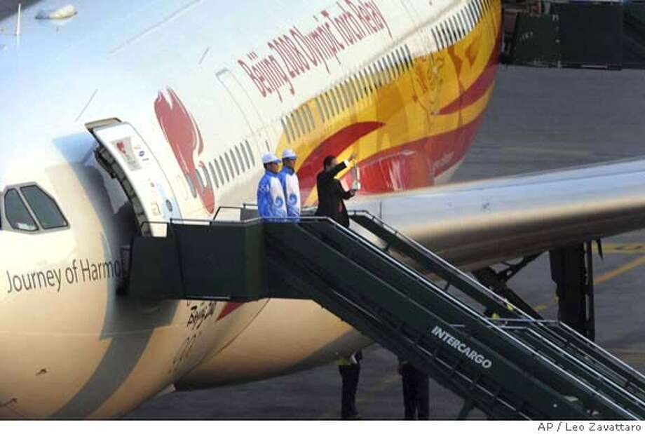 ###Live Caption:In this photo released by Argentina's Olympic Committee, a Chinese official holds up the Olympic torch upon its arrival at Buenos Aires International airport, Thursday, April 10, 2008. Argentine authorities are deploying 1,300 federal police, 1,500 naval police and some 3,000 traffic police and volunteers to protect the Olympic flame, an official said. (AP Photo/Leo Zavattaro/Argentina's Olympic Committee)###Caption History:In this photo released by Argentina's Olympic Committee, a Chinese official holds up the Olympic torch upon its arrival at Buenos Aires International airport, Thursday, April 10, 2008. Argentine authorities are deploying 1,300 federal police, 1,500 naval police and some 3,000 traffic police and volunteers to protect the Olympic flame, an official said. (AP Photo/Leo Zavattaro/Argentina's Olympic Committee)###Notes:###Special Instructions:EFE OUT - NO SALES - AP PROVIDES ACCESS TO THIS PUBLICLY DISTRIBUTED HANDOUT PHOTO. THE COPYRIGHT IS OWNED BY A THIRD PARTY Photo: Leo Zavattaro