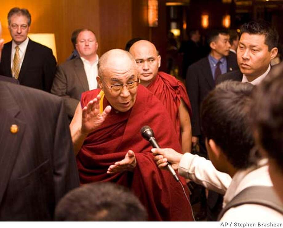 Flanked by security personnel, the Dalai Lama answers a reporter's question upon arriving at his hotel in Seattle, Thursday, April 10, 2008. (AP Photo/Stephen Brashear) Photo: Stephen Brashear