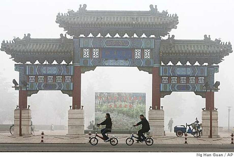 ** FILE ** Cyclists ride past a traditional Chinese gateway during a day murky from fog and pollution in Beijing, China, in this Oct. 26, 2007 file photo. Beijing, one of the world's most polluted cities, officials will halt construction, close heavy industries and even stop spray painting in order to clean the city's air before the Aug. 8, 2008, Summer Olympics begin. (AP Photo/Ng Han Guan, File) Photo: Ng Han Guan, AP