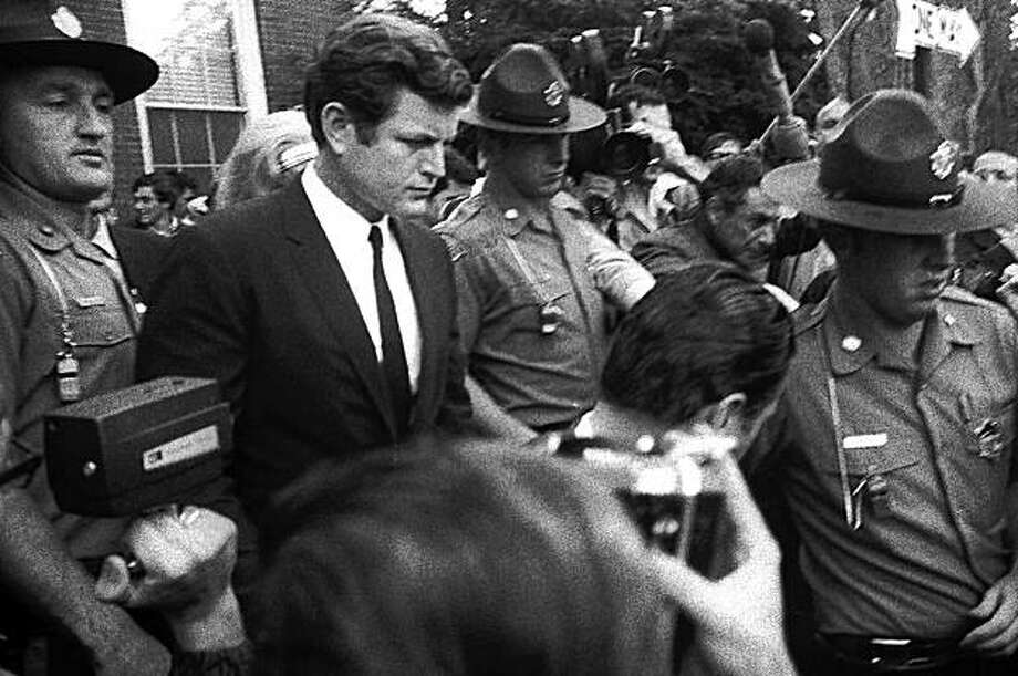 FILE--In a July 25, 1969 file photo Sen. Edward Kennedy is escorted by troopers as he leaves court in Edgartown, Mass., after pleading guilty to a charge of leaving the scene of the accident which killed aide Mary Jo Kopechne. Kennedy has died after battling a brain tumor his family announced early Wednesday Aug. 26, 2009. In a posthumous memoir, Massachusetts Sen. Edward M. Kennedy writes of fear and remorse surrounding the fateful events on Chappaquiddick Island in 1969, when his car accident left a woman dead, and says he accepted the finding that a lone gunman assassinated his brother President John F. Kennedy. (AP Photo/File) Photo: AP
