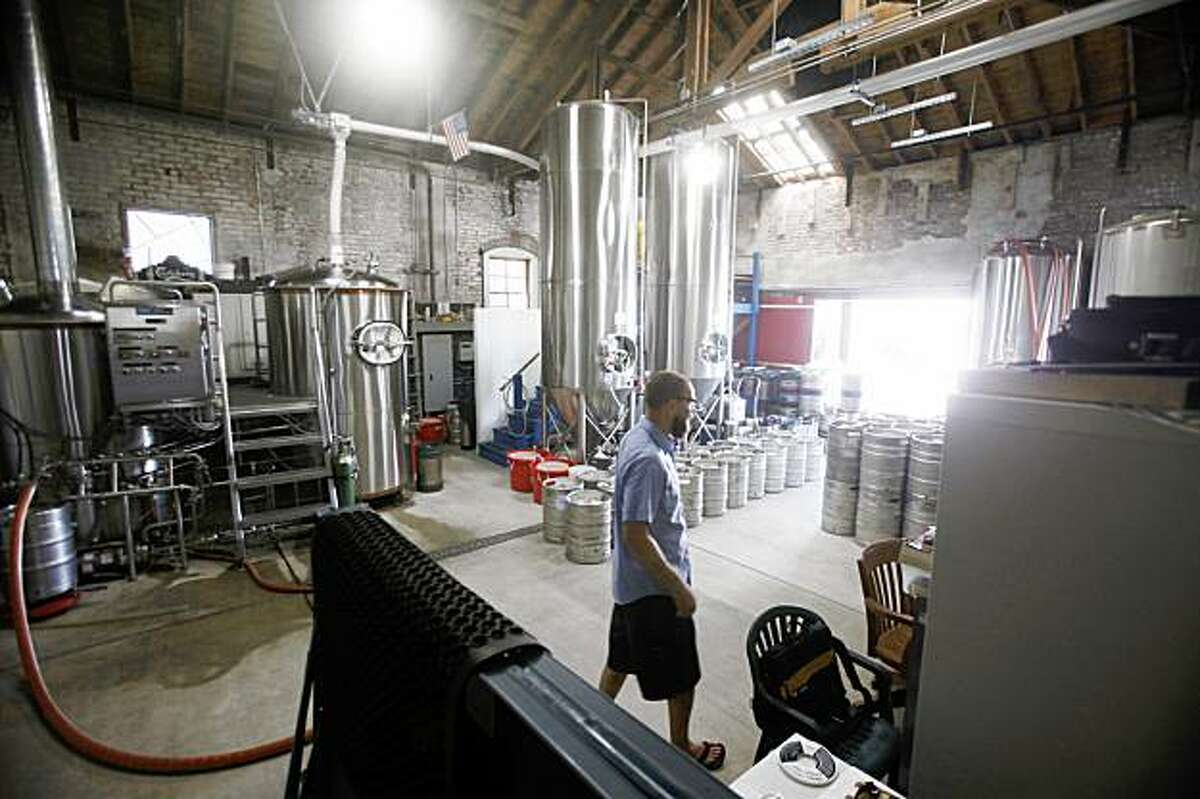 Adam Lamoreaux, brewer/owner of Linden Street Brewery checks the tanks on Tuesday Sept. 1, 2009 in Oakland, Calif.