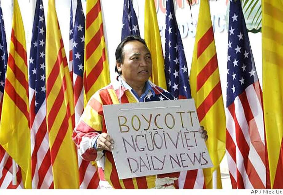 ###Live Caption:Protest organizer Ky Ngo stands in front of a row of American and South Vietnamese flags, during a protest outside Vietnamese-language newspaper Nguoi Viet Daily Wednesday, April 2, 2008, in Westminster, Calif. Hundreds of noisy protesters have picketed outside the Vietnamese-language newspaper for more than two months, ever since it published a picture of a bright yellow foot-washing basin lined with the South Vietnamese flag's three red stripes. (AP Photo/Nick Ut)###Caption History:Protest organizer Ky Ngo stands in front of a row of American and South Vietnamese flags, during a protest outside Vietnamese-language newspaper Nguoi Viet Daily Wednesday, April 2, 2008, in Westminster, Calif. Hundreds of noisy protesters have picketed outside the Vietnamese-language newspaper for more than two months, ever since it published a picture of a bright yellow foot-washing basin lined with the South Vietnamese flag's three red stripes. (AP Photo/Nick Ut)###Notes:###Special Instructions: Photo: Nick Ut