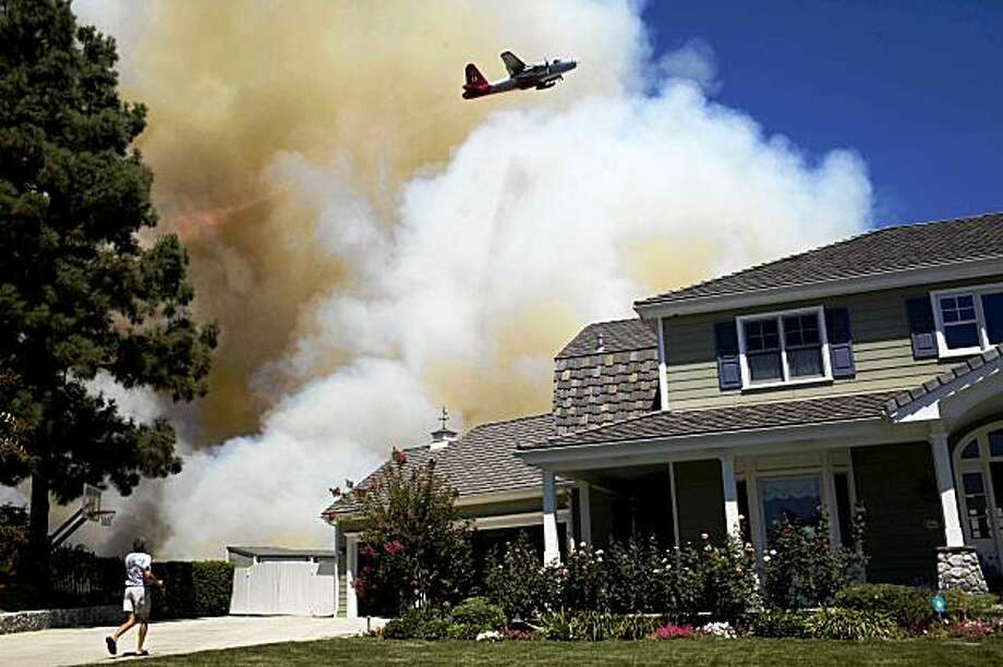 A man runs to gather his belongings as a fire threatens his home in the city of La Canada Flintridge Calif., from a wildfire in the San Gabriel Mountains 20 miles outside of downtown Los Angeles, Saturday, Aug. 29, 2009. (AP Photo/ Philip Scott Andrews) Photo: Philip Scott Andrews, AP