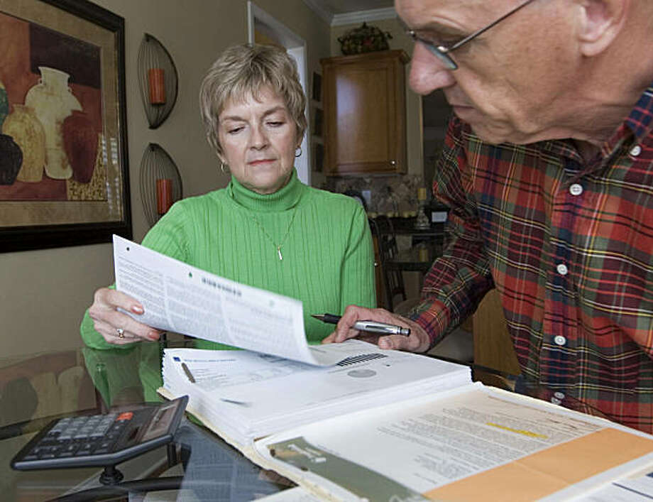 **FOR USE WITH AP LIFESTYLES**   Judy and Bob Dienell review their financial statements  Saturday, Oct. 25, 2008, in Braselton, Ga. During this economic crisis, with stocks on a scary roller-coaster ride, there seem to be two kinds of people: Those who are following the peaks and plunges of their investments and those who simply refuse to look.   (AP Photo/John Amis) Photo: John Amis, AP