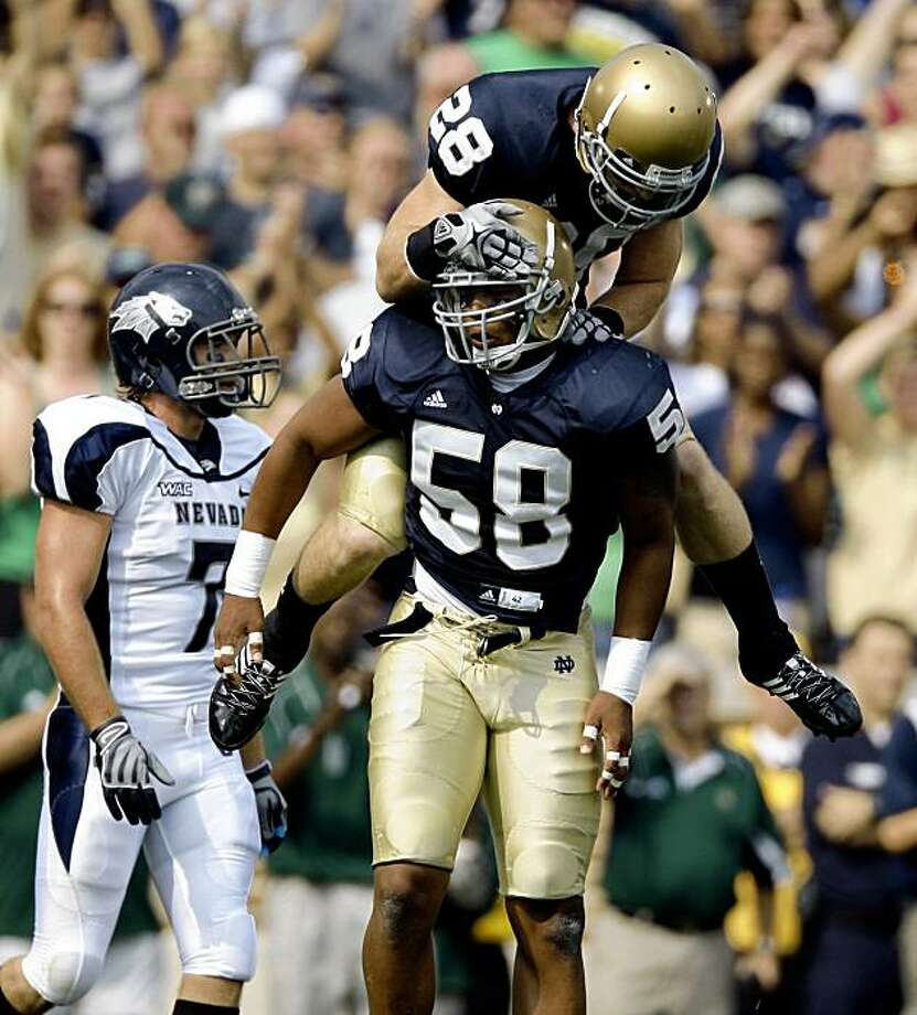 Notre Dame linebacker Brian Smith, bottom, and safety Kyle McCarthy celebrates after a sack in the first quarter against Nevada during an NCAA college football game in South Bend, Ind., Saturday, Sept. 5, 2009. (AP Photo/Michael Conroy) Photo: Michael Conroy, AP