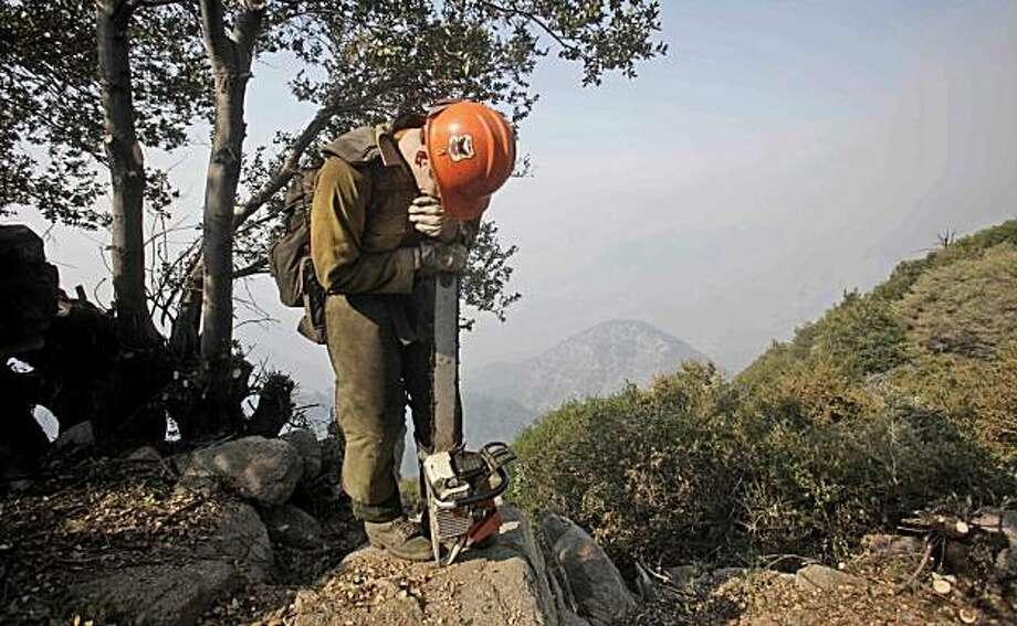 Firefighter Will Burks leans on his chainsaw before climbing down a steep section of the Angeles National Forest while his crew builds a fire break at Mt. Wilson, Calif., Wednesday, Sept. 2, 2009. Photo: LM Otero, AP