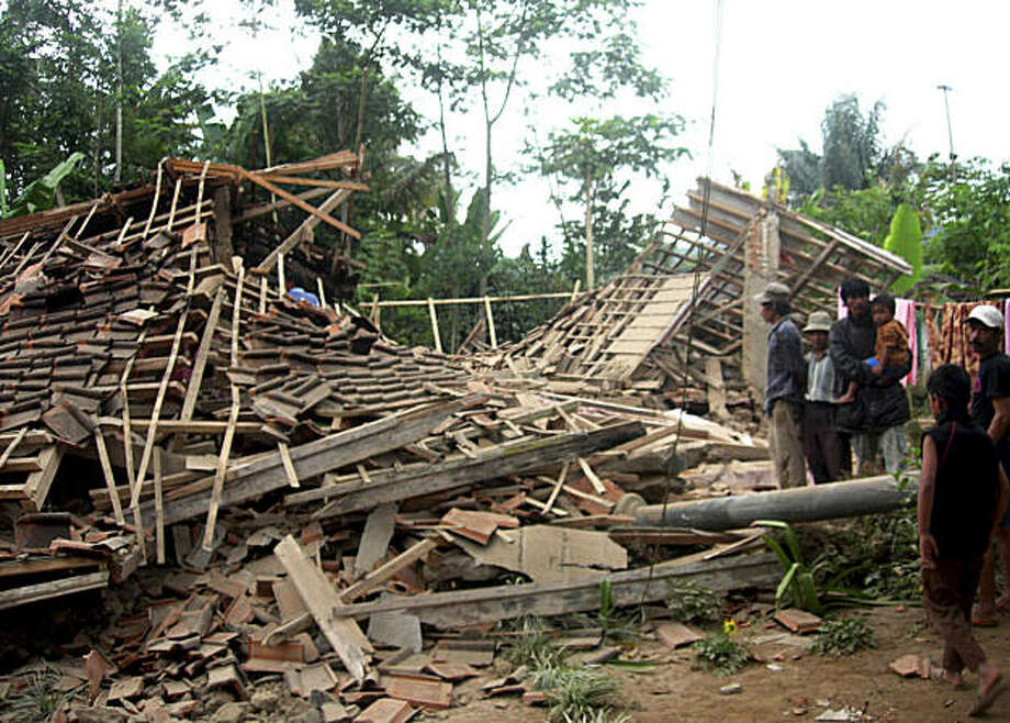 People stand outside a house destroyed by an earthquake in Tasikmalaya, West Java, Indonesia, Wednesday, Sept. 2, 2009. A powerful earthquake rattled southern Indonesia on Wednesday, killing at least 32 people crushed by falling rock or collapsed buildings and sending thousands fleeing outdoors for safety in the middle of the work day. (AP Photo/Pikiran Rakyat Daily) ** NO ARCHIVE NO SALES ** Photo: Pikiran Rakyat Daily, AP