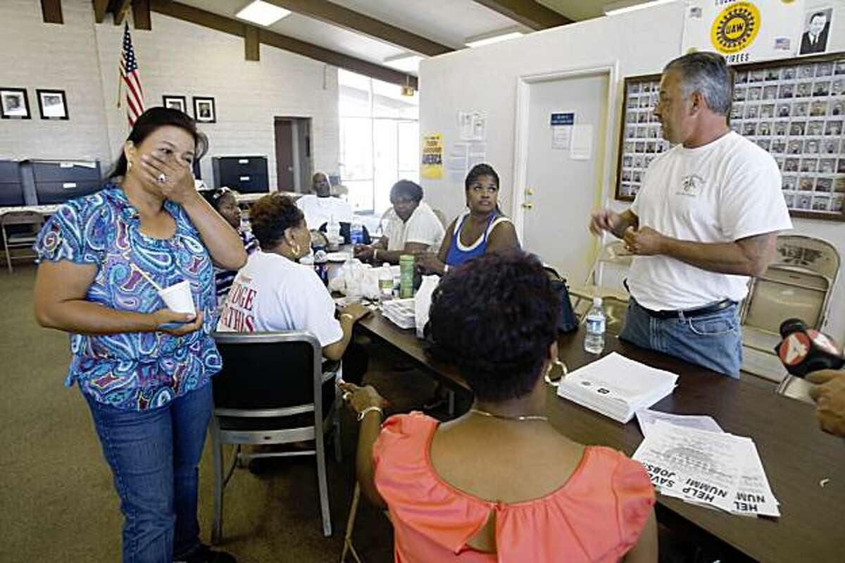 Edie Senadenos (left), who has worked with Nummi for 12 years, reacts as Ron Lopez (right), union trustee, talks with people from the rally task force at the UAW union hall in Fremont, Calif. on Thursday, August 27, 2009.