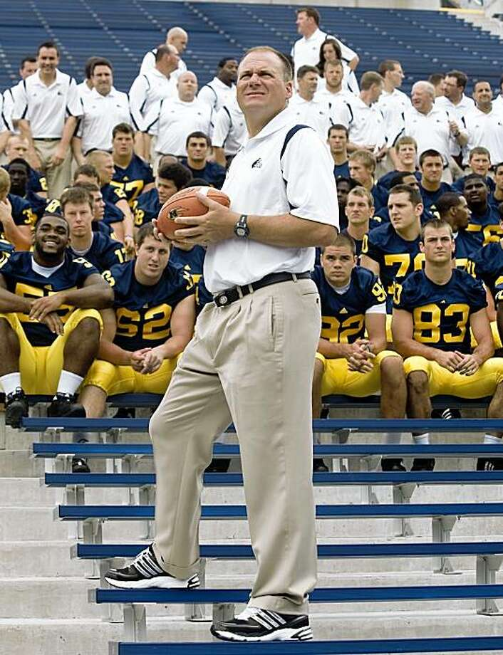 In this Aug. 23, 2009 photo, Michigan head coach Rich Rodriguez waits for his players to be seated for a team photo, during the school's annual football media day at Michigan Stadium in Ann Arbor, Mich. Players from the 2008 and 2009 teams told the Detroit Free Press for a story published on the newspaper's Web site on Saturday, Aug. 29, 2009 that the amount of time they spend on football activities during the season and in the offseason greatly exceeds NCAA limits. (AP Photo/Tony Ding) Photo: Tony Ding, AP