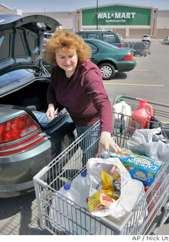 Rosemary Lyons fills her trunk after shopping at Wal-Mart in Clarence, N.Y., Thursday, April 10, 2008. With prices at the pump rising and worries about jobs increasing, shoppers bought basics at discounters and wholesale clubs and snubbed mall-based chains' clothing, jewelry and furniture. (AP Photo/David Duprey) Photo: David Duprey