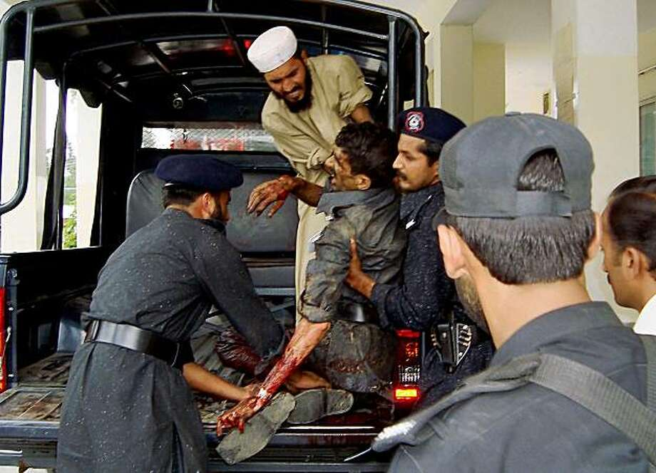 Pakistani police officers unload one of their injured colleagues at a local hospital in Saidu Sharif, a town in Pakistan's troubled Swat Valley, Sunday, Aug. 30, 2009. A suicide bomber killed more than a dozen community police recruits in Pakistan's Swat Valley in the deadliest attack since the army regained control over the northwestern valley from the Taliban, an official said. (AP Photo/Naveed Ali) Photo: Naveed Ali, AP