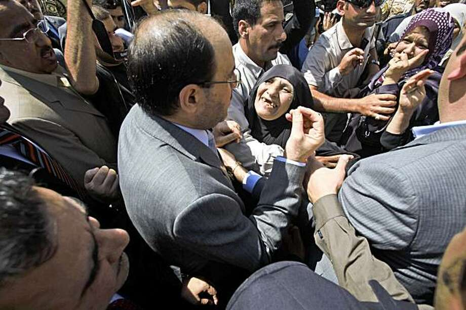 Iraqi Prime Minister Nouri al-Maliki, center, talks to families whose homes were destroyed in a truck bombing that targeted the foreign ministry in Baghdad, Iraq, Monday, Aug. 24, 2009. Major Shiite groups have formed a new alliance that will exclude the Iraqi prime minister, lawmakers said Monday, a move likely to stoke fears of increasing Iranian influence and shake up the political landscape ahead of January parliamentary elections. The announcement was a new setback for al-Maliki, whose efforts to portray himself as a champion of security has been battered by a series of devastating bombings in Baghdad and in northern Iraq in recent weeks. The most recent of these struck the foreign and finance ministries on Wednesday, killing about 100 people and wounding some 500. Photo: Karim Kadim, AP
