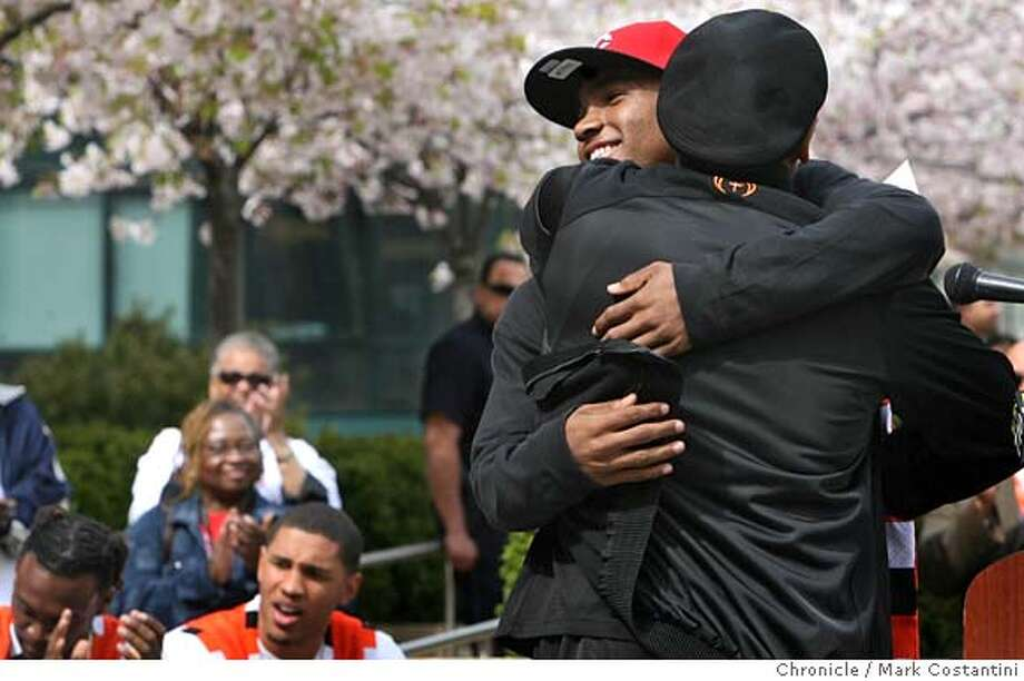 ###Live Caption:McClymonds high school boys basketball gaurd Quincy Hill smiles as he gets a hug from his coach ÊDwight Nathaniel at a rally at Oakland City Hall in Oakland, Calif. on April 4, 2008 celebrating the McClymonds boys basketball team, which was undefeated and won state championship. Photo by Mark Costantini / San Francisco Chronicle.###Caption History:McClymonds high school boys basketball gaurd Quincy Hill smiles as he gets a hug from his coach �Dwight Nathaniel at a rally at Oakland City Hall in Oakland, Calif. on April 4, 2008 celebrating the McClymonds boys basketball team, which was undefeated and won state championship. Photo by Mark Costantini / San Francisco Chronicle.###Notes:###Special Instructions:MANDATORY CREDIT FOR PHOTOG AND SAN FRANCISCO CHRONICLE/NO SALES-MAGS OUT Photo: Mark Costantini