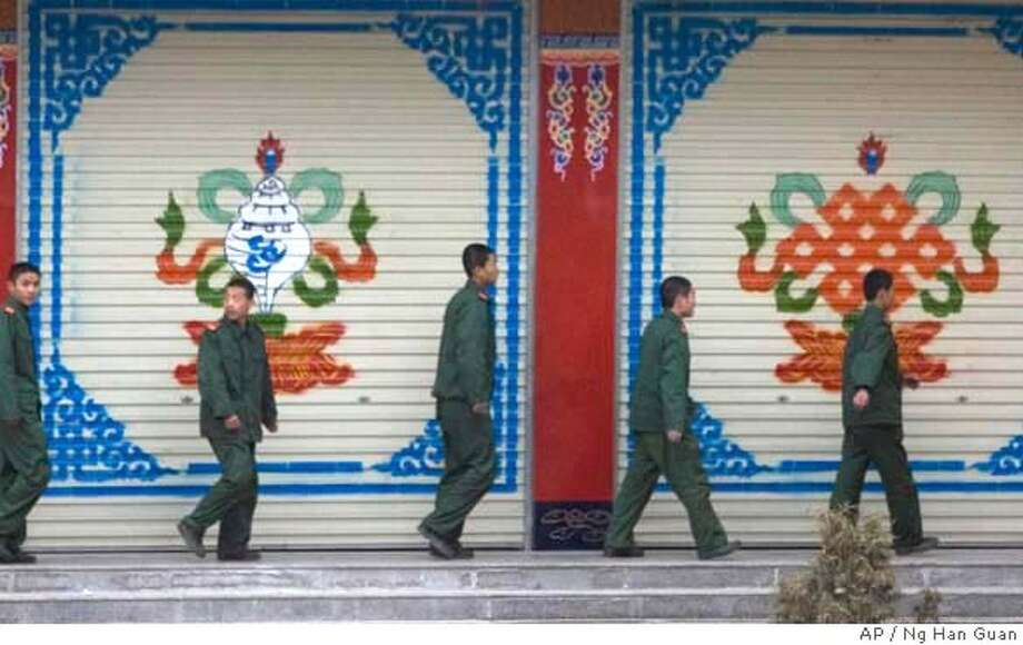 Chinese military officers walk near Tibetan symbols painted on shop fronts at a public square in Xiahe, western China's Gansu province, Thursday, April 3, 2008. Xiahe was the site of violent protest two weeks ago but calm has returned as Chinese troops maintain a strong presence around the Tibetan town and monasteries. (AP Photo/Ng Han Guan) Photo: Ng Han Guan