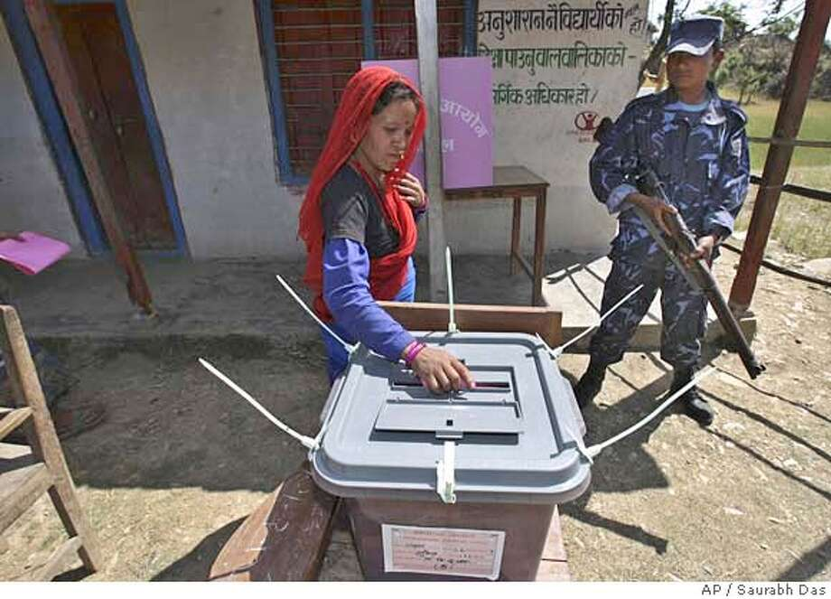 ###Live Caption:A woman casts her vote as an armed police officer watches in the former Maoist stronghold of Rolpa, Nepal, Thursday, April 10, 2008. The Maoists, contesting in this election as Communist Party of Nepal Maoist, had started their people's movement against the government in Rolpa. (AP Photo/ Saurabh Das)###Caption History:A woman casts her vote as an armed police officer watches in the former Maoist stronghold of Rolpa, Nepal, Thursday, April 10, 2008. The Maoists, contesting in this election as Communist Party of Nepal Maoist, had started their people's movement against the government in Rolpa. (AP Photo/ Saurabh Das)###Notes:###Special Instructions: Photo: Saurabh Das