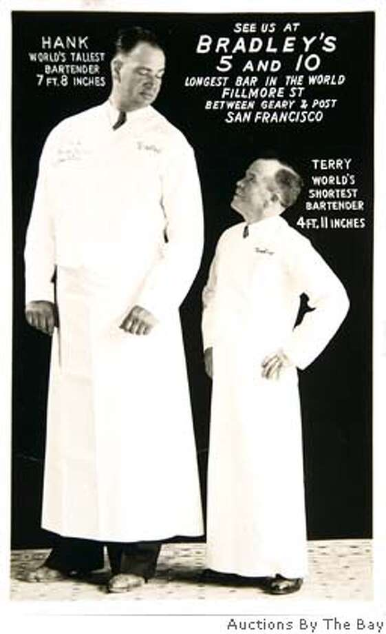 """anonymous 1930s postcard from Bradley's 5 and 10 bar in San Francisco showing Hank, """"world's tallest bartender'' and Terry, """"world's shortest bartender. Photo: Courtesy Auctions By The Bay"""
