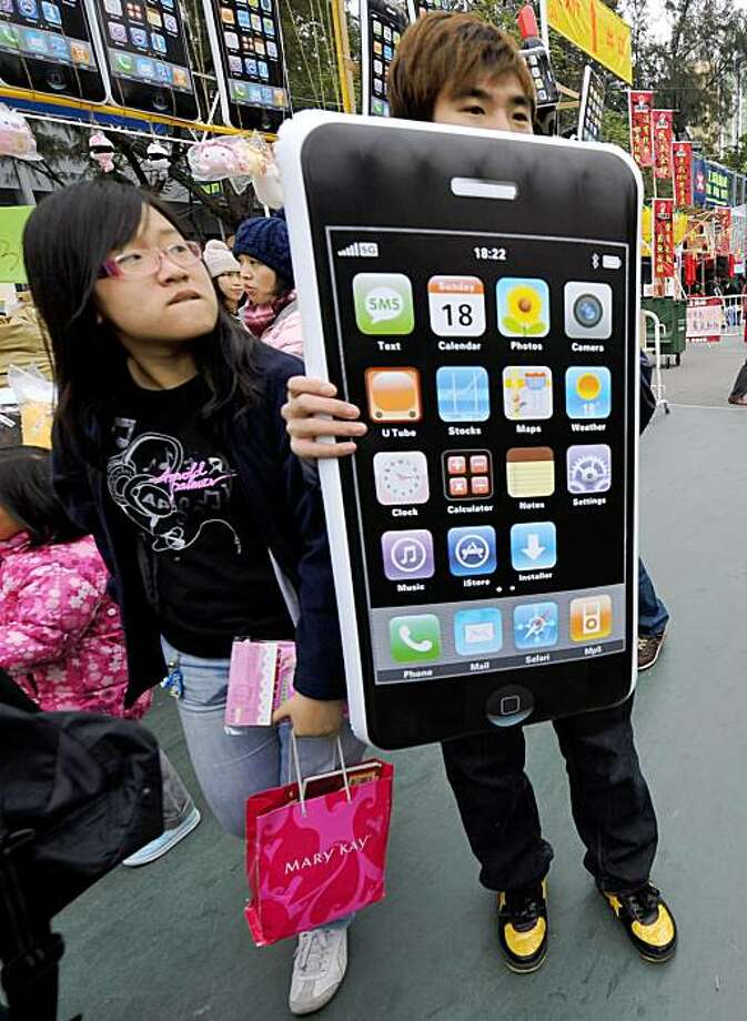 TO GO WITH STORY China-US-Telecom-company-Apple (FILES) In a file picture taken on January 24, 2009, a young girl looks at an inflatable iPhone decoration for sale at the Lunar New Year fair in Hong Kong. US high-tech giant Apple and China Unicom announced on August 28, 2009 they had reached a multi-year deal to launch the widely popular iPhone in the world's largest mobile market later this year. AFP PHOTO/TED ALJIBE (Photo credit should read TED ALJIBE/AFP/Getty Images) Photo: Ted Aljibe, AFP/Getty Images