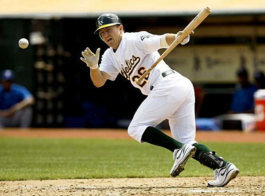 Oakland Athletics' Cliff Pennington lays down a bunt single off Texas Rangers starting pitcher Tommy Hunter during the third inning of a baseball game in Oakland, Calif., Thursday, Aug. 6, 2009. (AP Photo/Marcio Jose Sanchez) Photo: Marcio Jose Sanchez, AP