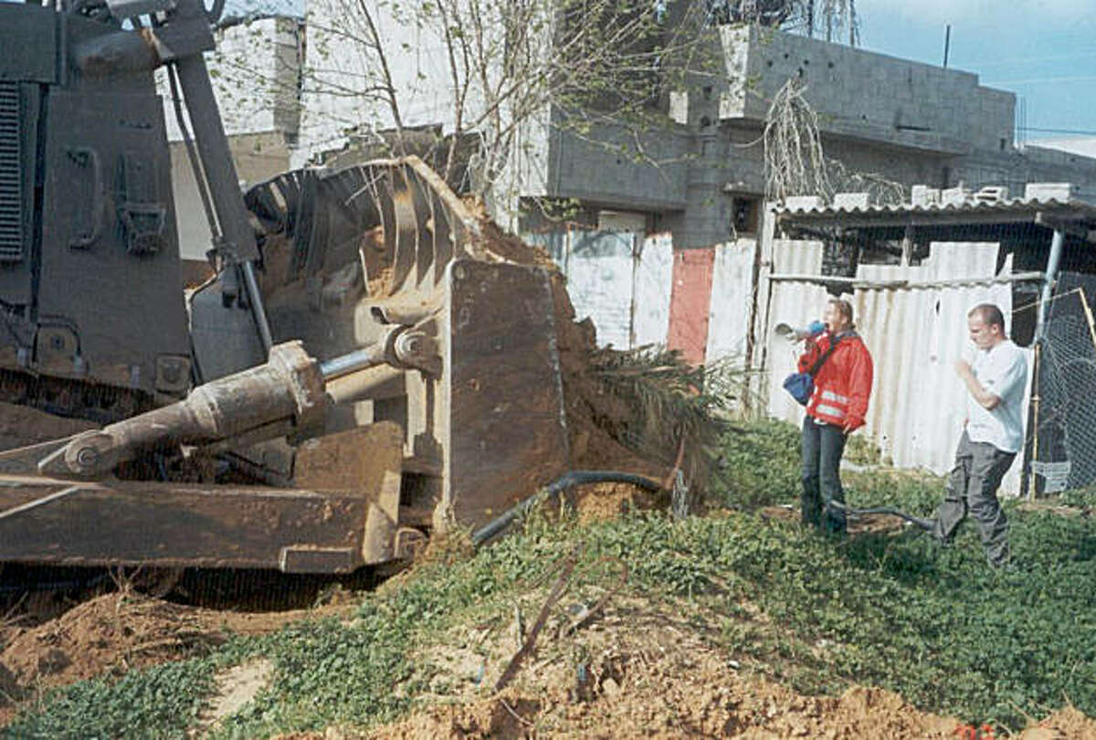 """** ONE OF SIX HANDOUT PHOTOS ** Rachel Corrie, 23, from Olympia, Wash., a member of the """"International Solidarity Movement,"""" uses a loudspeaker as she stands between an Israeli buldozer and a Palestinian physician's house in the southern Gaza Strip town of Rafah Sunday, March 16, 2003. Corrie died Sunday while trying to stop a bulldozer from tearing down the physician's home. She fell in front of the machine, which ran over her and then backed up, witnesses said.(AP Photo/HO, International Solidarity Movement) ALSO RAN: 3/18/03"""
