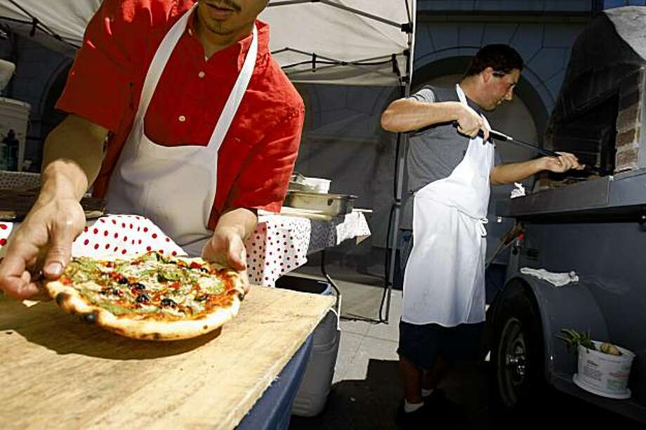 Dung Tran (left) cashier, prepares a pizza for a customer as lead cook, Aaron Lerch (right), monitors pizzas in the oven at the Pizza Politano booth at the Ferry Building Farmers' Market in San Francisco, Calif. on Thursday, August 13, 2009. Photo: Lea Suzuki, The Chronicle