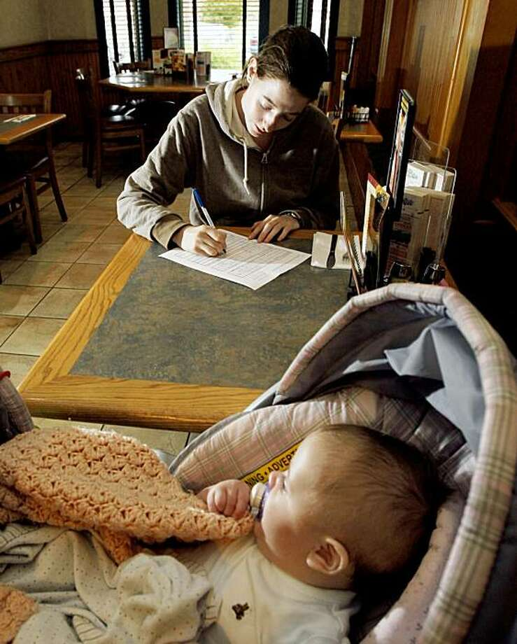 FILE - In this Aug. 13, 2009 file photo, Sarah Robillard, 19, of Pawtucket, R.I. fills out a job application while her four-month-old baby sits at the Ground Round Restaurant in Pawtucket. The number of newly laid-off workers filing claims for unemployment benefits rose unexpectedly for the second straight week, an indication that jobs remain scarce.(AP Photo/Elise Amendola, file) Photo: Elise Amendola, AP