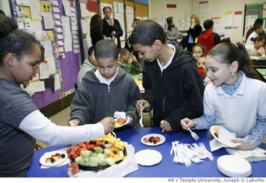 ###Live Caption:** FOR RELEASE MONDAY,APRIL 7 AT 12:01 A.M. ** Students from Philadelphia's Fairhill School fourth graders, from left to right; Gabrielle Hudnell, Erick Ramirez, David Barroso and Asle Torres snack on fresh fruit during a nutrition education activity on Tuesday, April 1, 2004.. Participating schools offered students only snacks with 7 grams of fat or less. (AP Photo/Joseph V. Labolito /Temple University)###Caption History:** FOR RELEASE MONDAY,APRIL 7 AT 12:01 A.M. ** Students from Philadelphia's Fairhill School fourth graders, from left to right; Gabrielle Hudnell, Erick Ramirez, David Barroso and Asle Torres snack on fresh fruit during a nutrition education activity on Tuesday, April 1, 2004.. Participating schools offered students only snacks with 7 grams of fat or less. (AP Photo/Joseph V. Labolito /Temple University)###Notes:###Special Instructions:NO SALES AP provides access to this publicly distributed HANDOUT photo to be used only to illustrate news reporting or commentary on the facts or events depicted in this image. Photo: Joseph V. Labolito