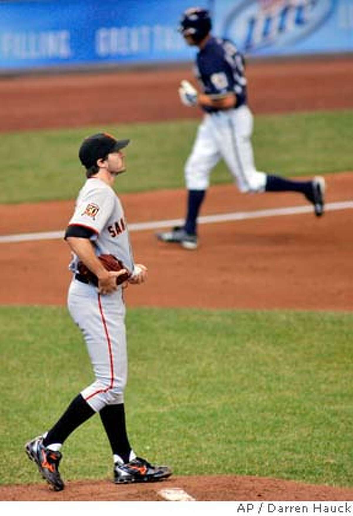 Milwaukee Brewers' Ryan Braun, right, rounds third base after hitting a home run against San Francisco Giants starting pitcher Barry Zito, left, in the fifth inning of the baseball game Sunday, April 6, 2008, in Milwaukee. (AP Photo/Darren Hauck)