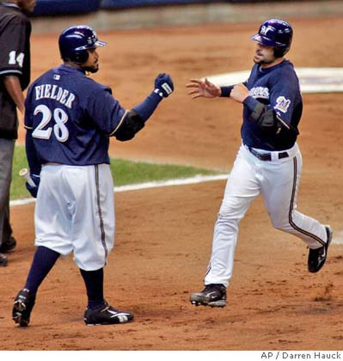 Milwaukee Brewers' Jason Kendall, right, is congratulated by Prince Fielder, left, after scoring on a sacrifice fly during the third inning of a baseball game against the San Francisco Giants on Sunday, April 6, 2008, in Milwaukee. (AP Photo/Darren Hauck)