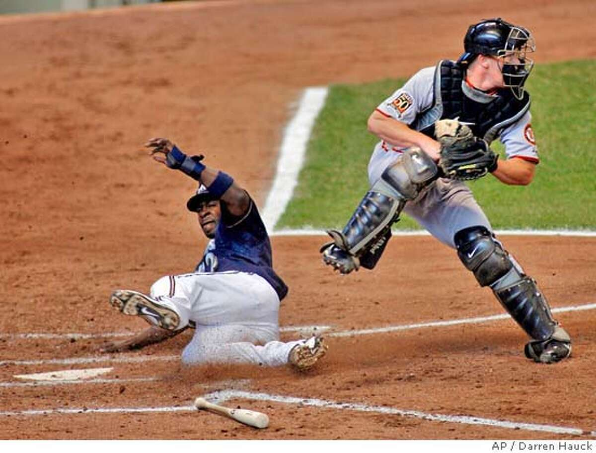 Milwaukee Brewers' Bill Hall slides after being forced out at home by San Francisco Giants catcher Stephen Holm, right, on a ground ball by Ben Sheets in the fourth inning of a baseball game Sunday, April 6, 2008, in Milwaukee. (AP Photo/Darren Hauck)
