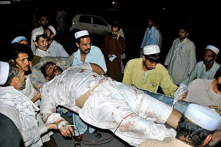 Pakistani people carry an injured victim of the suicide blast outside a hospital in Peshawar on August 27, 2009. A suicide bomber killed at least 21 policemen in Pakistan's northwestern tribal region as they gathered to break their Ramadan fast officials said. AFP PHOTO/K.B. BUTT (Photo credit should read K.B. BUTT/AFP/Getty Images) Photo: K.B. Butt, AFP/Getty Images