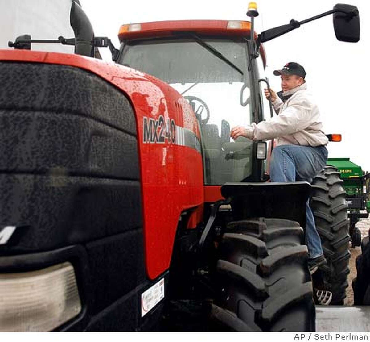 Cental Illinois corn and soybean farmer Larry Gleason inspects one of his tractors on his farm in Elkhart, Ill., Monday, March 31, 2008. The U.S. Department of Agriculture expects Illinois farmers to plant less corn this spring and more soybeans, following a national trend. (AP Photo/Seth Perlman)